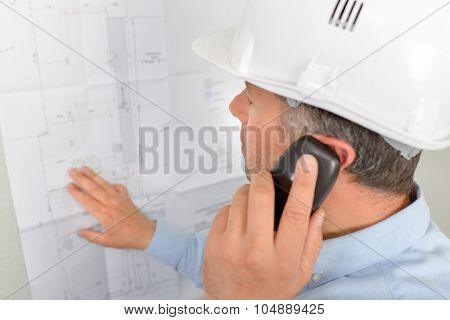 Man on phone looking at plans