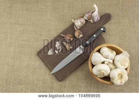 Knife, Garlic and a Cutting Board. Chopped garlic and a knife on a wooden board
