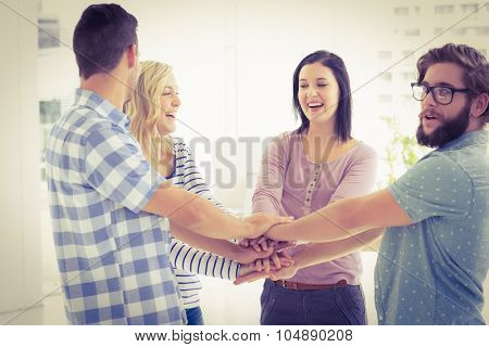 Smiling business people putting their hands together in office