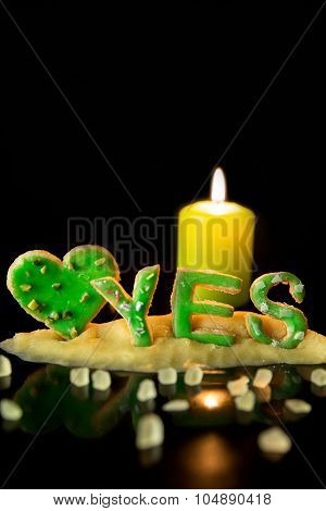 Cookie Letters With Cookie Dough And A Candle, Word Yes With A Heart In Front Of Black Background