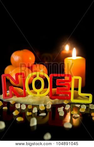 Cookie Cutter Building The Word Noel, Tangerines And Candle, Black Background, Concept Christmas