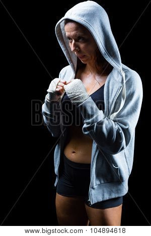 Female fighter in hood with fighting stance against black background