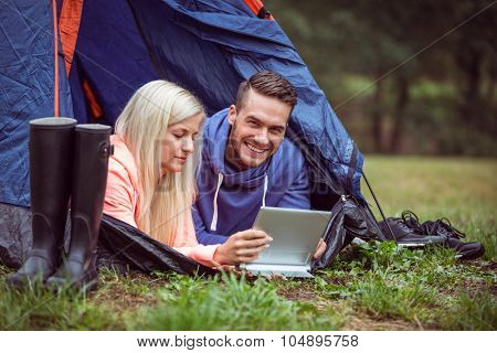 Happy couple lying in their tent using tablet in the countryside