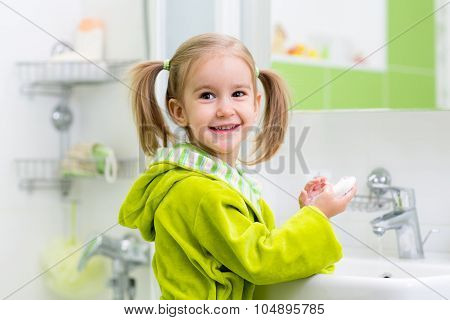 kid washing her face and hands in bathroom