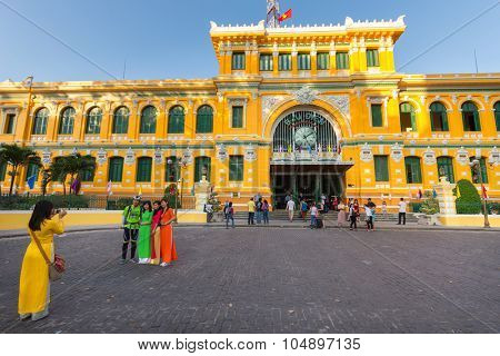 HO CHI MINH, VIETNAM, FEBRUARY 25, 2015 : The central French colonial style post office with Vietnamese girls in traditional Ao Dai dresses taking some photos in Ho Chi Minh city (Saigon), Vietnam
