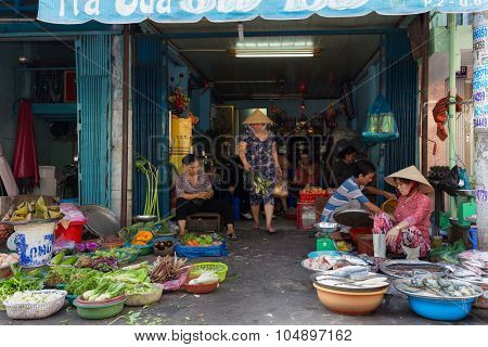 HO CHI MINH VILLE, VIETNAM, FEBRUARY 26, 2015 : A family is selling vegetables and fishes in the street at the  Cho Binh Tay market in the Chinatown district of Ho Chi Minh Ville, (Saigon), Vietnam.