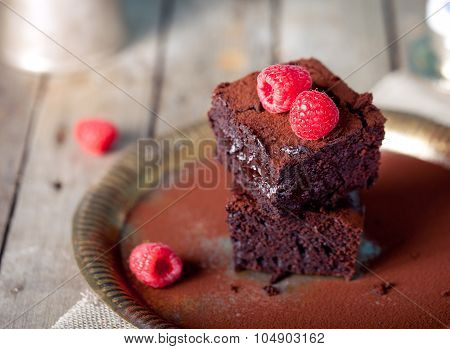 Brownies with raspberry on a wooden background.