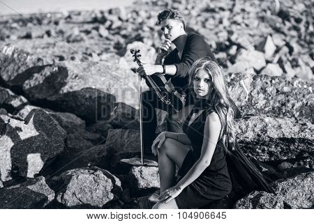violinist and the girl sitting on stones