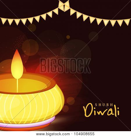 Glossy illuminated oil lit lamp on shiny brown background for Indian Festival of Lights, Happy Diwali celebration.