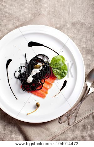 Cuttlefish ink paste with cream sauce and salmon