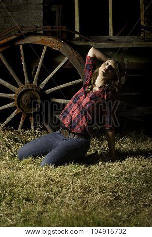 Sexy farm girl posing in front of old wagon