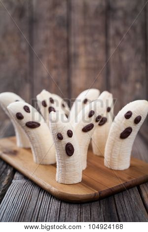 Scary halloween banana ghost chocolate faces healthy natural snack recipe. Delicious party decoratio