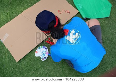 Young Woman Drawing On The Grass