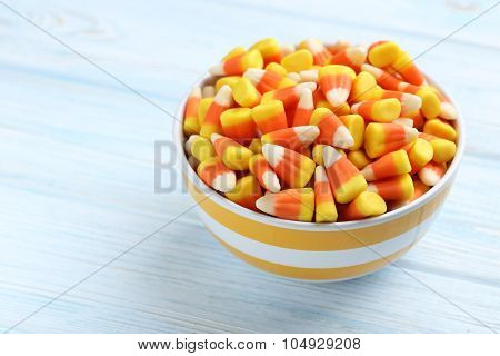 Halloween Candy Corns In Bowl On Blue Wooden Background