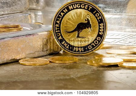 Australian Gold Nugget Coin With Silver Bars In Background