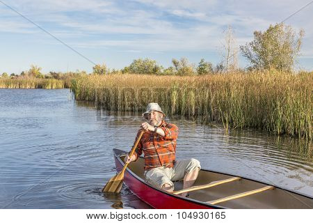senior paddler enjoying paddling a red canoe on a calm lake, Riverbend Ponds Natural Area, Fort Collins, Colorado