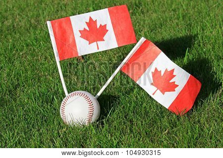 Baseball with Canadian Flags on a grass Field