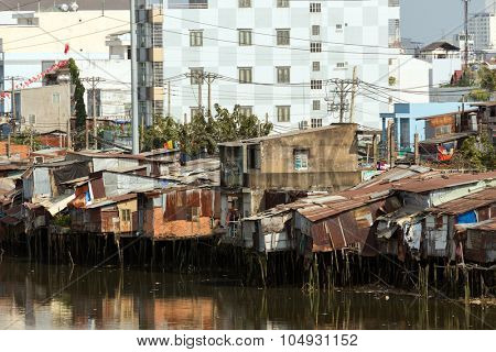 Slum wooden house on the Saigon river bank, in front of modern buildings, in Ho Chi Minh city, Vietnam