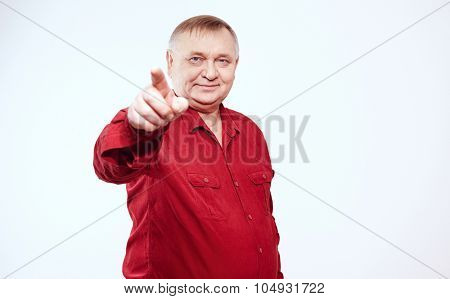 Aged man wearing red shirt standing and pointing at camera with his index finger against white background - choice concept