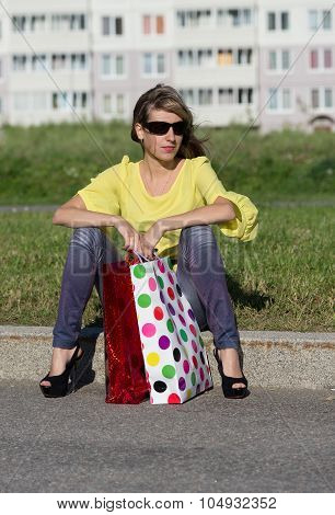 Woman Sitting On Border With Shopping Bags