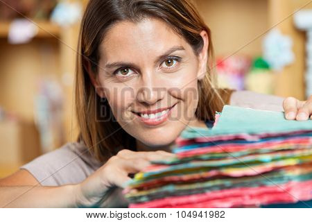 Portrait of smiling mid adult saleswoman with colorful papers in shop