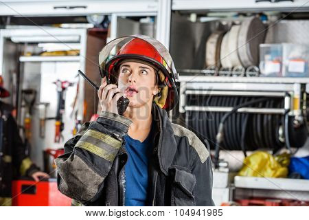 Confident female firefighter looking up while using walkie talkie at fire station