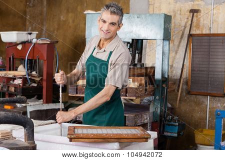 Portrait of happy worker stirring pulp and water with stick in paper factory