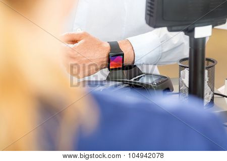 Midsection of male customer paying through smartwatch in pharmacy