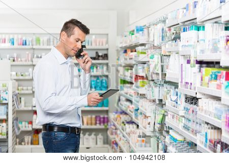 Mid adult male customer using mobile phone and digital tablet in pharmacy
