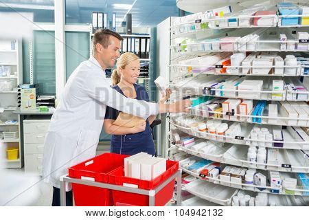 Happy male pharmacist and female assistant counting stock in pharmacy