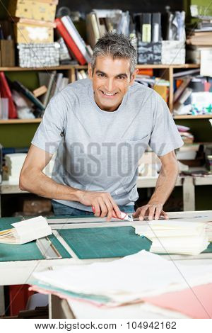 Portrait of happy mature male worker cutting paper at table in factory