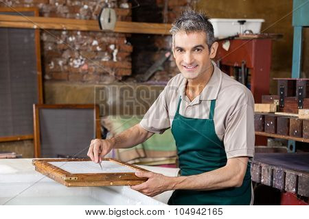 Portrait of confident mature male worker cleaning paper with tweezers in factory