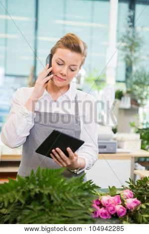 Female florist using mobile phone and digital tablet at counter in flower shop