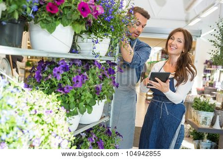 Male and female workers using digital tablet in flower shop