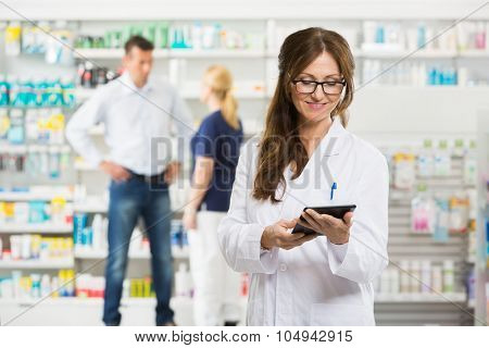 Female pharmacist holding digital tablet while assistant and customer standing in background at pharmacy