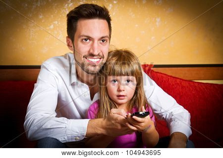 Little Girl And Her Borther Watching Tv At Home
