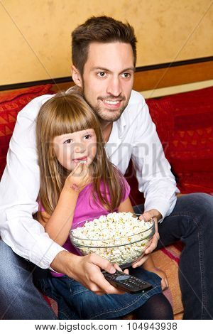 Little Girl And Her Borther Enjoy Eating Popcorn And Watching Tv At Home