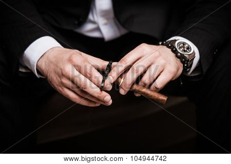 elegant man wearing black suit and white shirt cut Cuban cigar indoor shot, closeup