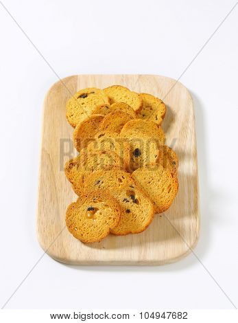 heap of bread rusks with black olives on wooden cutting board