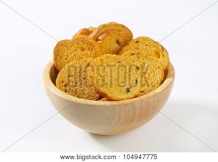 bowl of bread rusks with black olives on white background
