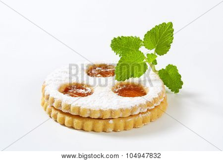 close up of linzer cookie with strawberry jam on white background