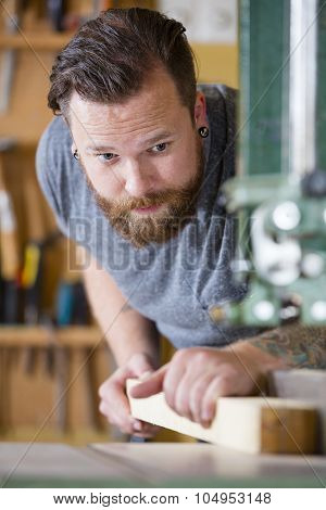 Craftsman using bandsaw for splitting wood plank in workshop