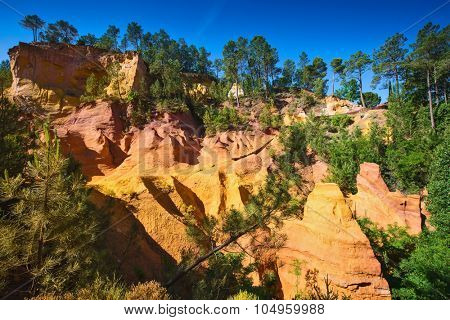 Unique red and orange hills in the province of Languedoc - Roussillon, France. Green trees create a beautiful contrast with the bright ocher