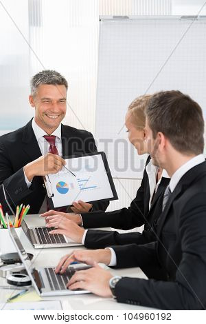 Businessman Explaining Graph To His Co- Workers