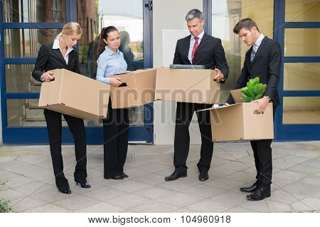 Unhappy Businesspeople With Cardboard Boxes Outside The Office