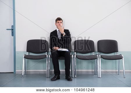 Businessman Yawning While Sitting On Chair