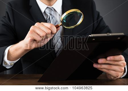 Businessperson Inspecting Document With Magnifying Glass