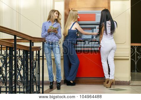 Three young beautiful modern girls using an automated teller machine. ATM, Women withdrawing money or checking account balance