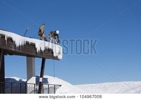 SOCHI, RUSSIA - JANUARY 22, 2015: Industrial climber take off the snow and icicles from the roof