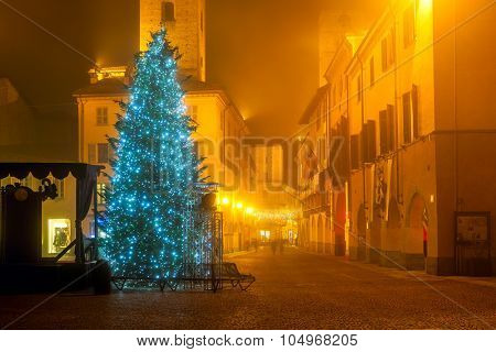 Illuminated Christmas tree on town square on foggy evening in Alba, Piedmont, Northern Italy.
